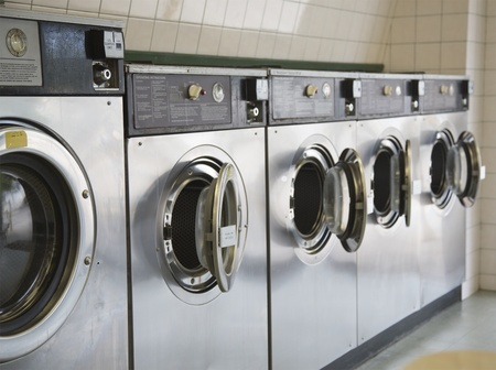 row of steel front loading washers in a laundromat