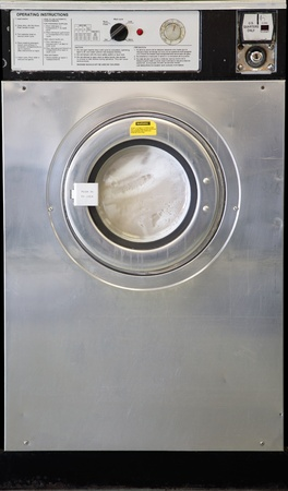 a used industrial washing machine with clothes inside being washed