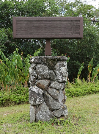 a blank wooden sign in a park in hawaii on a stand made of lava rock Standard-Bild