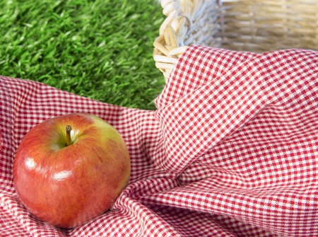 Red apple sitting on a checkered tablecloth in next to a wicker basket with grass in background Stock Photo