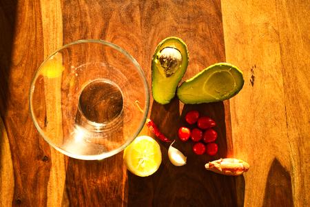 Zutaten für eine Guacamole. Chili, Zitrone, Zwiebel und Avocado auf einem Holztisch. Hausgemachtes mexikanisches Essen.