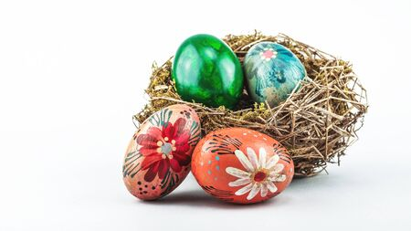 Old Easter eggs in bird nest isolated on a white background. Stock fotó