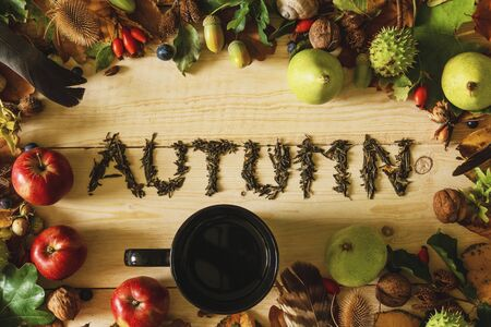 Autumn concept. A black cup of tea on a wooden table with a frame of autumn crops and falling leaves.