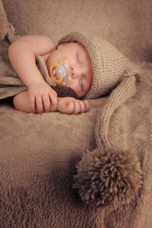 Sleeping baby with pacifier in knitted hat with pom pom. Vertical format. Banco de Imagens