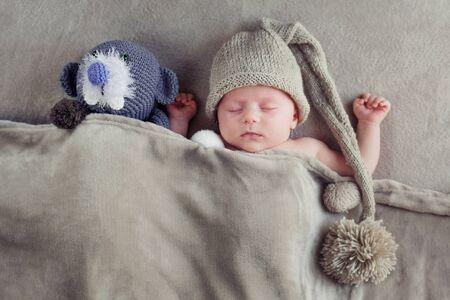 Bebé durmiendo con un gorro de punto con un pompón con un juguete debajo de una manta gris. Vista desde arriba.