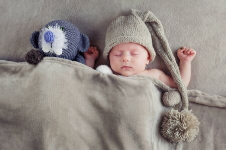 Sleeping baby in a knitted cap with a pompom with a toy under a gray blanket. View from above.