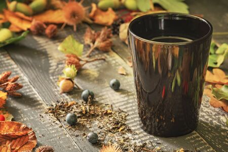 Black cup with tea on old weathered wooden table with spilled tea framed by colorful fallen leaves and autumn crops.