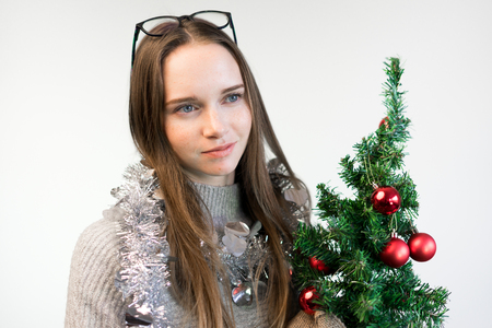 a girl with a small Christmas tree is cunning