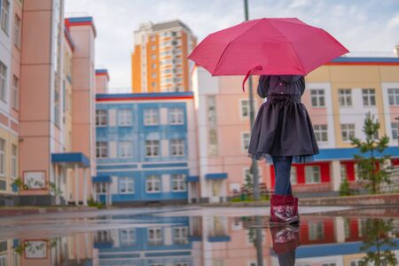 Girl mysteriously holds red umbrella covering face, rain