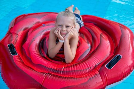 Beautiful kid sits on an air mattress and swims in an open pond in summer on vacation, hot