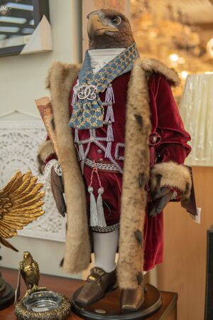 An eagle in a royal mantle in a short fur coat stands on two legs in shoes Stock Photo