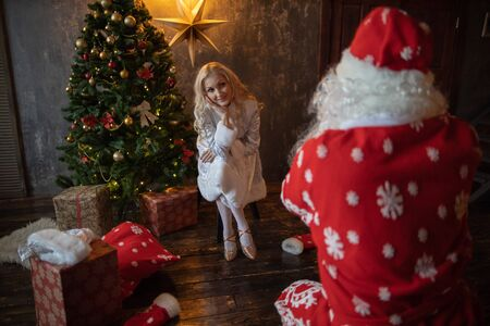 Santa Claus have fun near the Christmas tree and beautiful Snow Maiden Banco de Imagens - 135980187