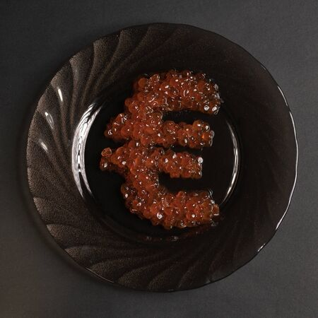 The euro symbol is made of red caviar on a black plate on a gray background over looking from above. Food in the worlds elite restaurants is a symbol of money