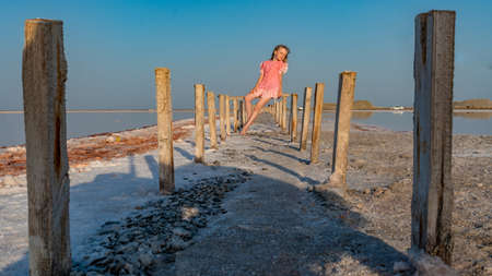 Salt Lake, the girl sitting barefoot in a red dress on wooden sticks, pondered