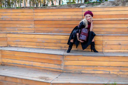 A happy girl sits on a summer theater bench, made of wood, in a burgundy coat and biret, an adult with tender lips, in the fall against a background of blue clouds.