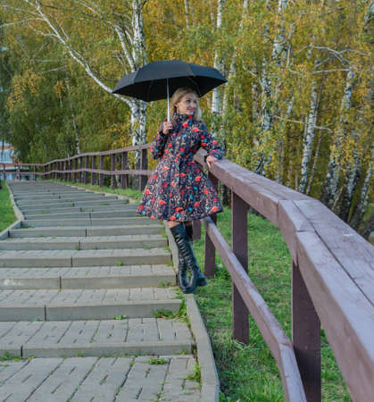 Funny girl with an umbrella stands in a dol fence on the stairs in a jacket in the fall. Yellow forest, green grass, blonde. with beautiful eyes the concept of comparison