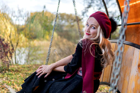 A beautiful woman sits on a garden swing, forged in a burgundy coat and biret, an adult smiles at the camera, in the fall against a background of blue clouds.