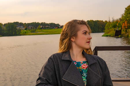 Cheerful young woman standing near the water smiling at the camera with a Caucasian appearance in a coat in the fall on the pier in the afternoon