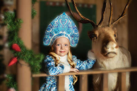 Daughter of Santa Claus with deer in blue Christmas card, with cones in blue
