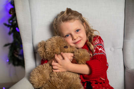 Girl hugs Teddy bear in red sweater for Christmas