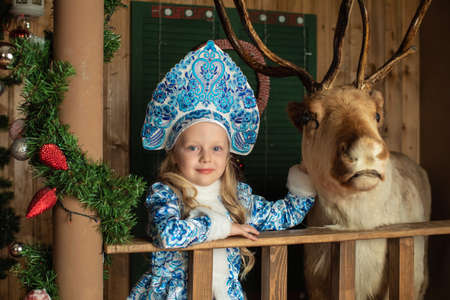 Girl dressed as Christmas snow maiden with deer in the house 版權商用圖片