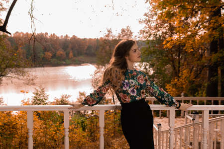Cheerful girl stands leaning against a white railing young looks at the camera blonde, in a colored shirt, standing against the background of autumn steps sensual standing bright blue eyes
