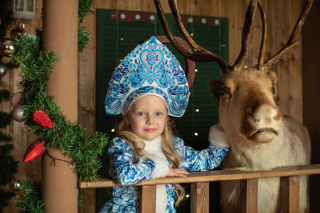 Girl with a deer at the Santaklaus festival in a blue snow-girl costume, a beautiful New Years Christmas