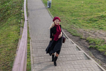 A happy girl walks up the stairs and in burgundy pall and biret, with beautiful eyes in black clothes, in the fall against the background of a pond, blue clouds. Stock fotó