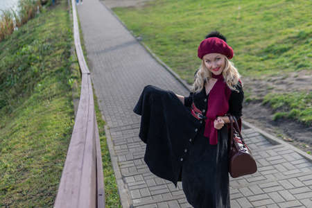 A smiling woman is walking up the stairs and wearing a burgundy palette and biret, looking at the camera in black clothes, in the fall against a blue sky. Stock fotó