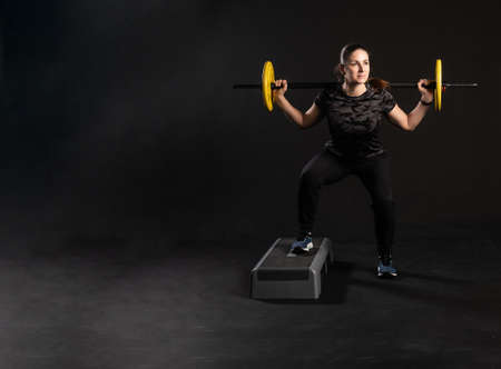 Fitness on a step platform, with a barbell, yellow pancakes holds equipment. Is engaged in sports on a black background Beautiful smiling at the camera