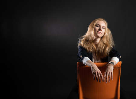 A young girl is sitting on an orange chair. Joyful with a wonderful smile, enjoy the concept, on a black background in the studio, in pedjak business woman, blonde