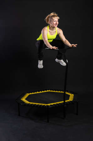 Girl on a fitness trampoline on a black background in a yellow t-shirt trampoline gym active exercise athlete cardio, cute club. Fly mini physical muscle instructor enjoy