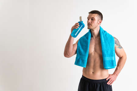 Male drink-water fitness is pumped with a towel on a white background isolated strong workout water healthy sportswear nutrition person, muscles hydration. protein caucasian one muscle