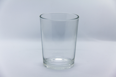 Empty glass of water with a reflection of LED strip on its rim on white background with horizontal separation shadow.