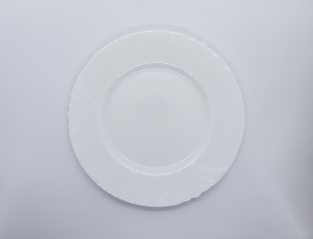 White plate on  white background with LED strip reflections on its edges.