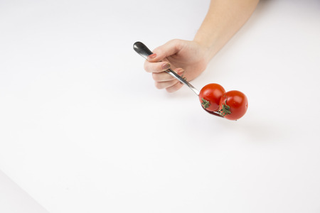 A hand is holding a fork with red tomatoes on a white background