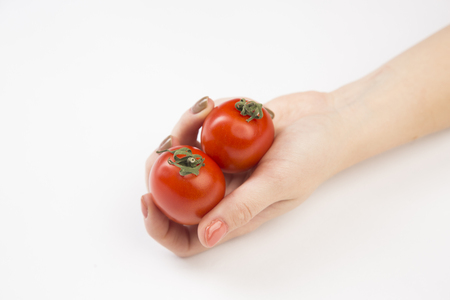 Red tomato gently in your hand on a white background