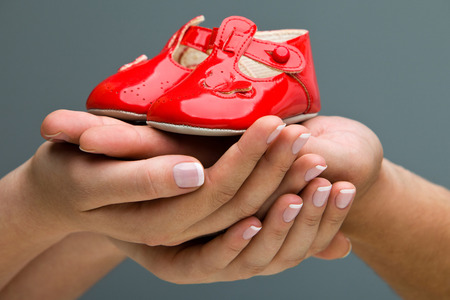 Woman and her husband holding baby shoes in their hands  Mom and Dad Expecting a baby  photo