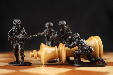 Toy soldiers kill chess King  Death of king  The dark does to the white chess king a checkmate  Stock Photo