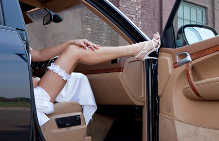 Wedding  Bride s leg in a garter and a shoe on a car s door  Young lady sitting out of the car  photo