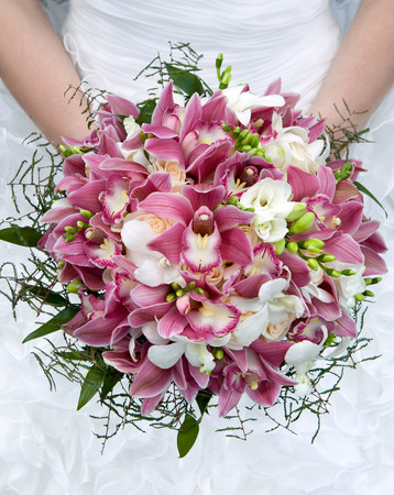 Wedding bouquet  Bouquet of fresh flowers for the wedding ceremony  Bouquet of orchids, roses and other flowers in the bride s hands closeup  Bridal bouquet  photo