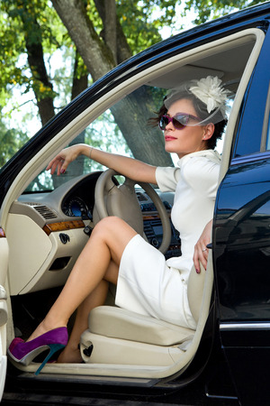 Elegant girl - the driver  Woman driving a car in a sheath dress with a hat veil and sunglasses  photo