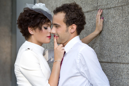 passionately: Stylish bride passionately presses the groom against the wall