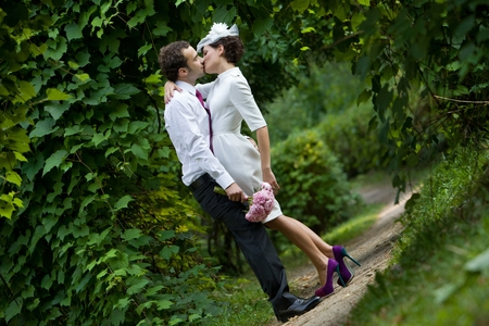 Wedding theme  The groom kisses the bride in a botanical garden  photo