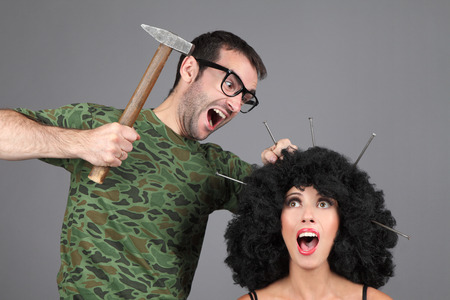 Concept - Idea  Creative team at work  Man is hammering nails into a girl s head  photo