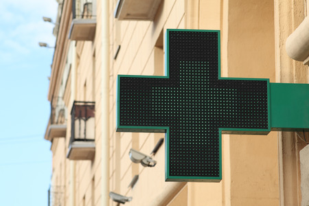 cross street with care: Pharmacy sign on the street  Green pharmacy sign