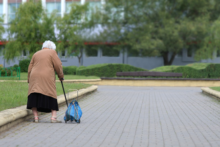 grandmothers: Old age - no joy  Old woman with bag seen from behind  Old woman tired  Stock Photo