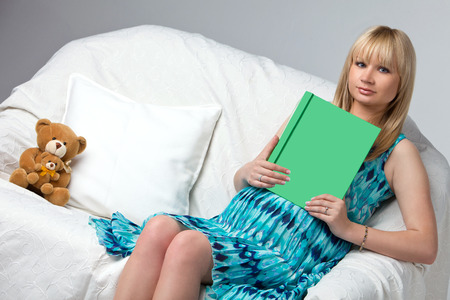 Pregnant woman reading a book on sofa  A book with a green screen for the inscriptions
