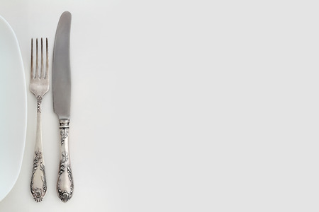Vintage fork and knife near the plate  Overhead view  Background with free text space  photo