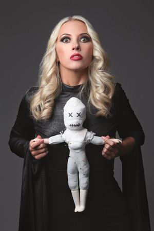 deadman: Witch holding a voodoo doll  Costume for Halloween Party  Blond witch  Portrait of Halloween woman looking at camera